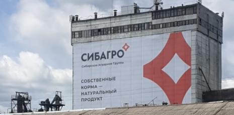 Печать сверхширокоформатного рекламного баннера и монтаж на фасад в городе Асино, Томская область